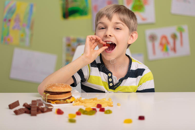 Child eating sweets and fastfood. Photo of content child eating sweets and fastfood royalty free stock images