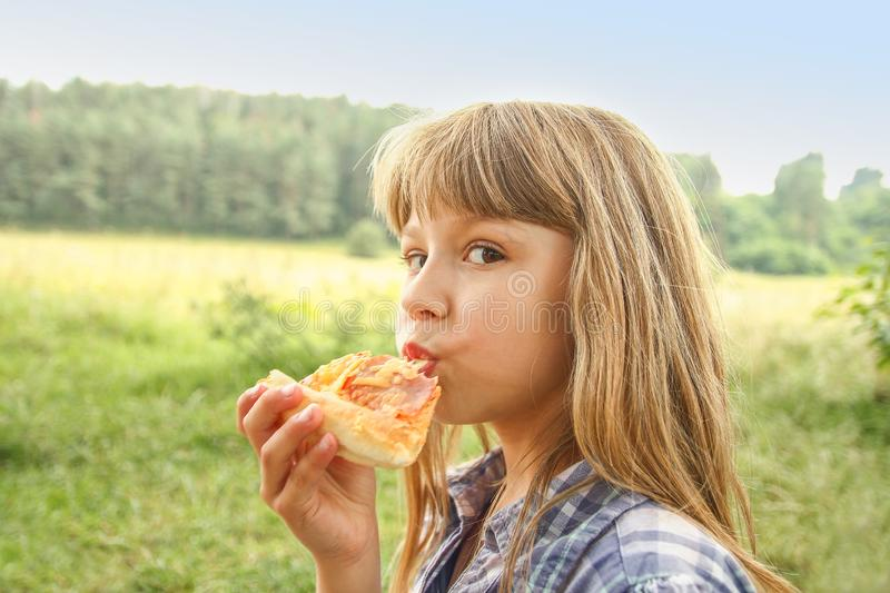 Child eating a tasty pizza on the nature of the grass in the park royalty free stock photography