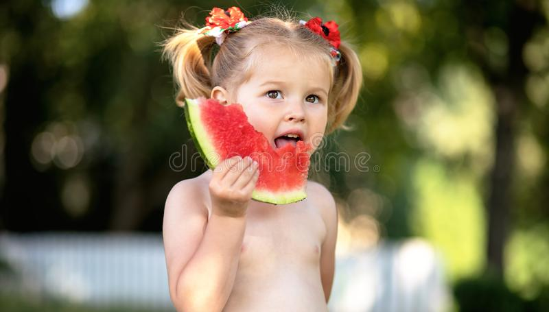 Child eating watermelon in the garden. Kids eat fruit outdoors. Healthy snack for children. Little girl playing in the garden hold royalty free stock photography