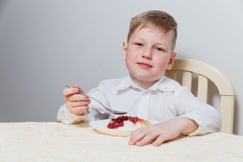 The child eats for breakfast, rice porridge with jam stock image