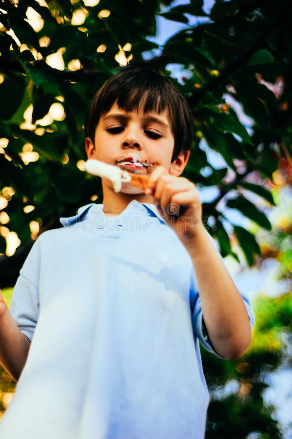 Child eats ice cream on a summer day in the shade of a tree stock image