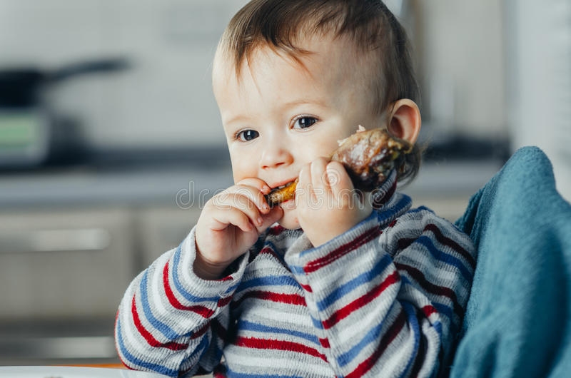 The child eats Lunch,meat chicken. The child greedily eating chicken, fatty and delicious in the kitchen, very hungry stock images