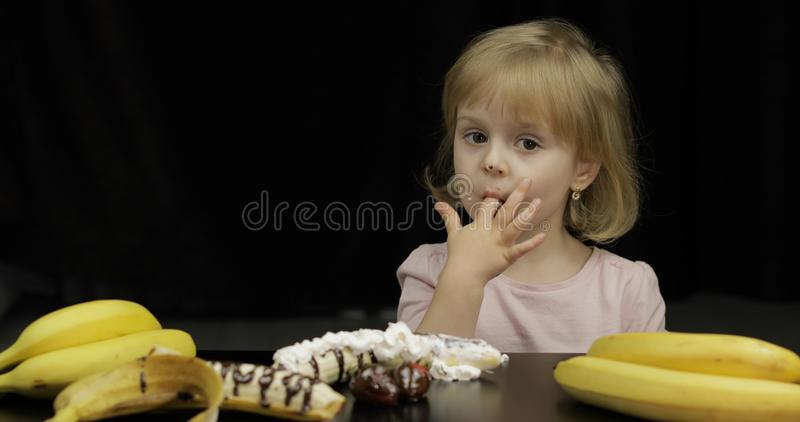 Child eats melted chocolate and whipped cream. Dirty face stock photography