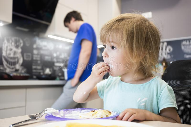 Child eats pancakes in the kitchen with pleasure royalty free stock photo