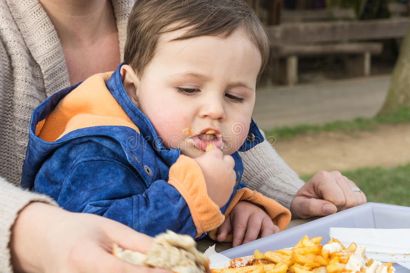 Child eats sausage with french fries royalty free stock photography