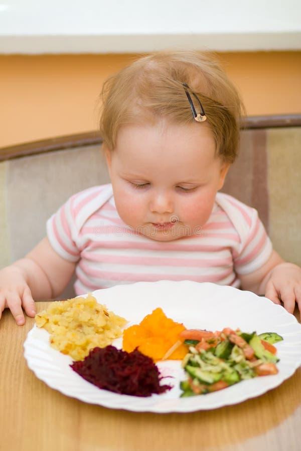 The child eats a vegetable salad. The litle child eats a vegetable salad stock photos