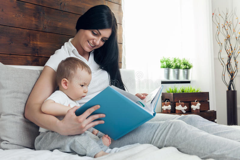 Child education. Happy mother with her toddler sitting on the bed and reading a book royalty free stock images