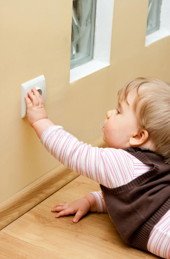 Child at electric socket. Dangerous situation - little child touching an electric socket in the wall royalty free stock images