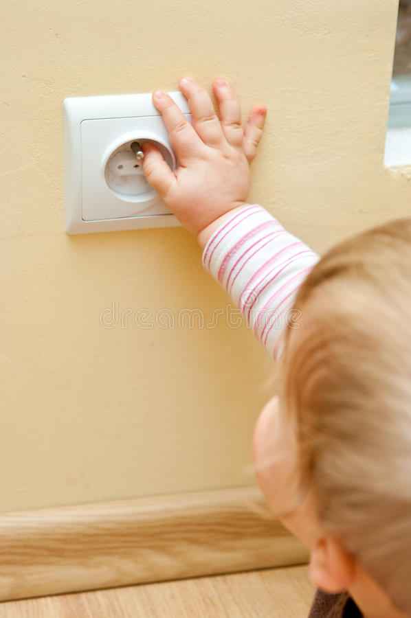 Child at electric socket. Dangerous situation - little child touching an electric socket in the wall royalty free stock image