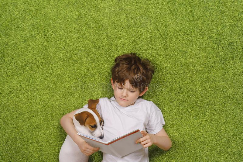Child embracing friendly dog jack russell was reading the book royalty free stock photo