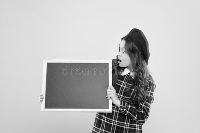 Child with empty blackboard. announcement. parisian child on yellow copy space. happy girl with long curly hair in beret stock image