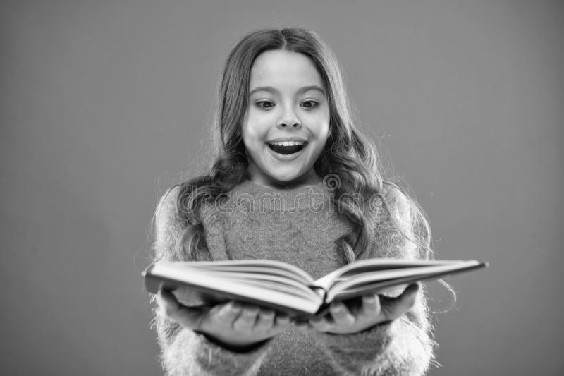 Child enjoy reading book. Book store concept. Wonderful free childrens books available to read. Childrens literature. Reading activities for kids. Girl hold stock photo