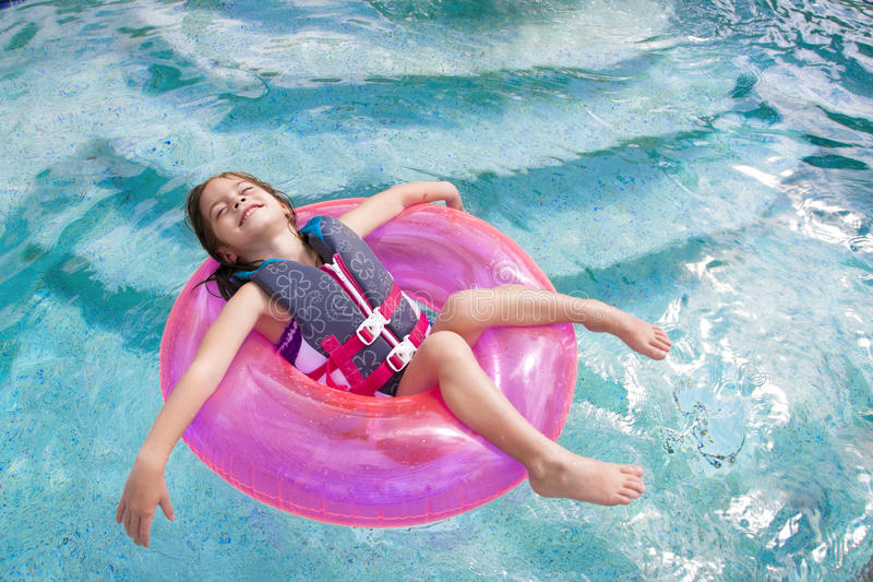 Child enjoying playing in the swimming pool. A cute little girl enjoying the summer sun while playing in the swimming pool floating on a pink floatation tube stock photos