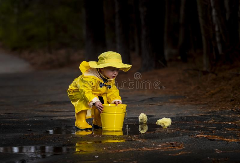 Child Enjoying The Rain In His Galoshes royalty free stock images