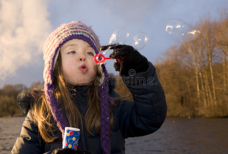 Child enjoys playing with soap bubbles at sunset stock photos
