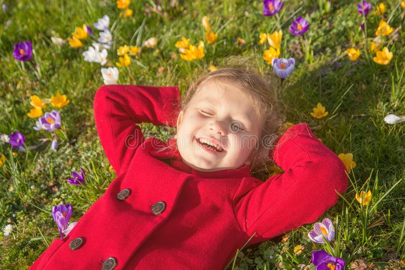 Child enjoys spring, sun and flowers. First flowers and happy children stock images