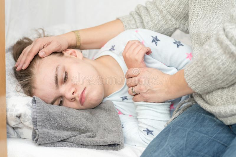 A child with epilepsy during a seizure. A child being cared for during an epileptic seizure by a qualified special needs carer royalty free stock photo