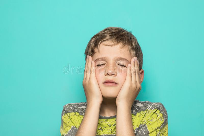 A child expressing a firing squad with his hands on his face. Kid with his hands on his face stock photo