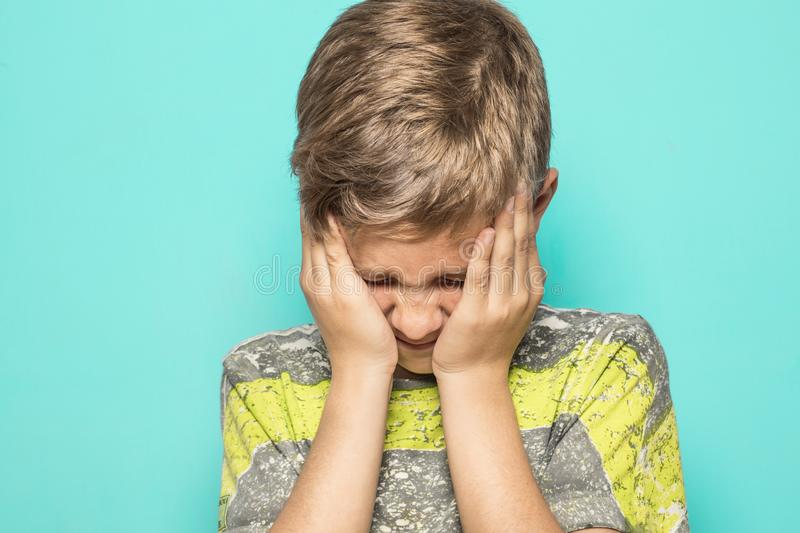 A child expressing a firing squad with his hands on his face. Kid with his hands on his face royalty free stock photography
