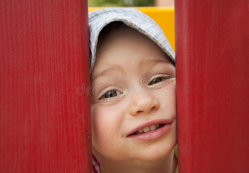 Child face. Face of small child, boy or girl, looking through a poles in an outdoors playground stock photography
