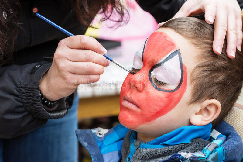 Child face painting. Face painting artist painting a child as spiderman royalty free stock photo
