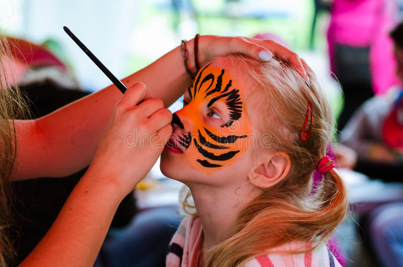 Child with face painting of tiger royalty free stock photography