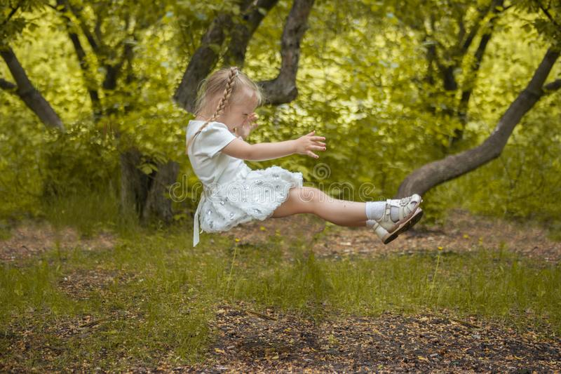 the child falls. fear of falling. growth in a dream. little girl in all whit stock image