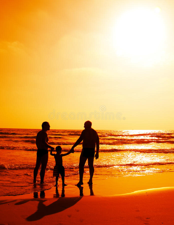 Child with father and grandfathe. R on the beach watching the sunset stock images