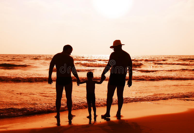 Child with father and grandfathe. R on the beach watching the sunset stock image