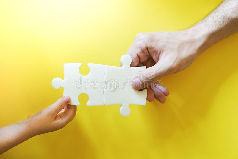 Child and father hands taking pieces of puzzle. royalty free stock image