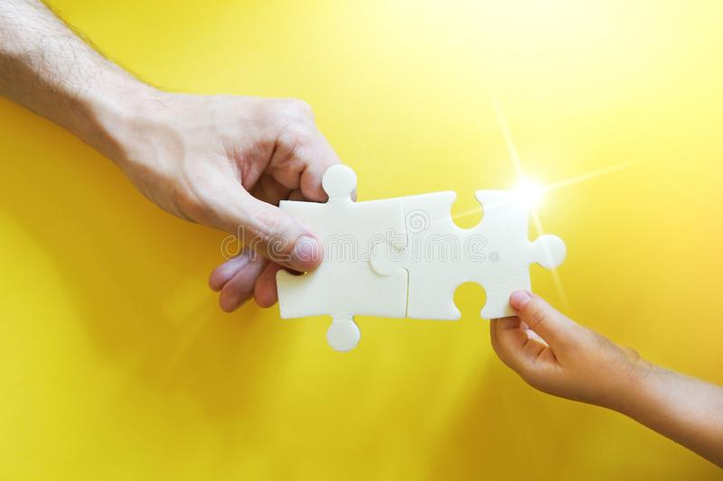 Child and father hands taking pieces of puzzle. stock image