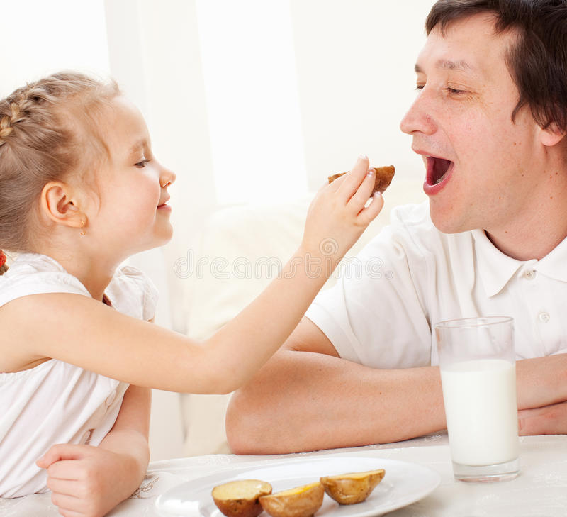Child with father have a breakfast. Family eating at home stock photos