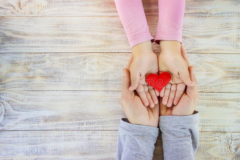 Child and father have a heart in their hands. Selective focus royalty free stock photos