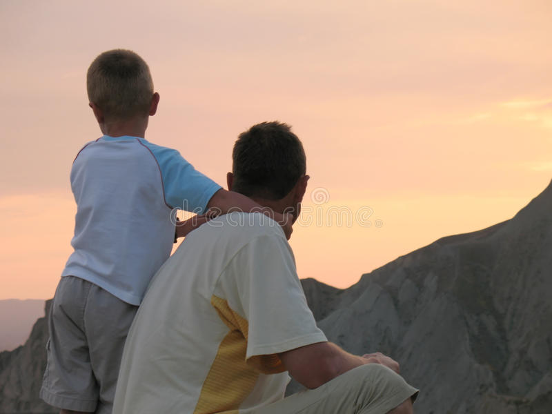 Child and father looking on sunset. Sky stock images