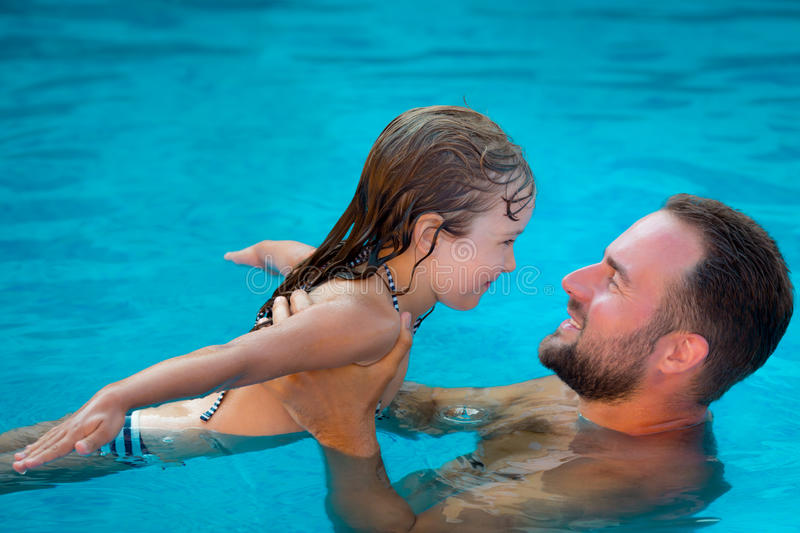 Child and father playing in swimming pool. Happy child and father playing in swimming pool. Summer vacation concept royalty free stock image