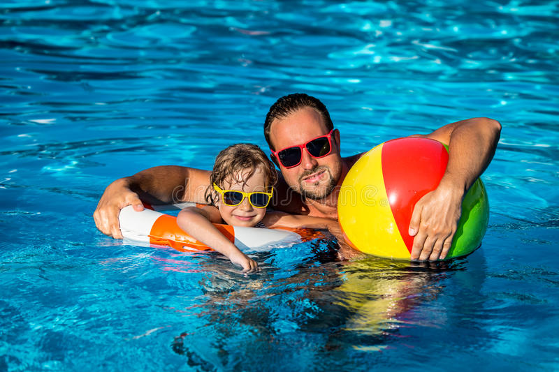 Child and father playing in swimming pool. Happy child and father playing in swimming pool. Summer vacation concept royalty free stock photography