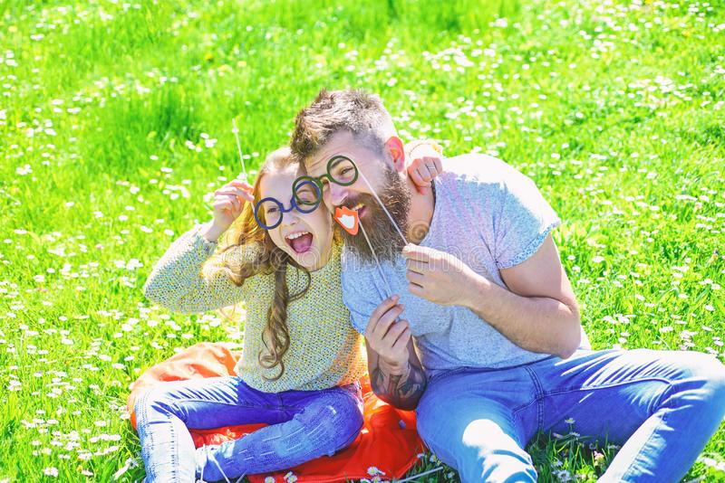 Child and father posing with eyeglases photo booth attributes at meadow. Smart and clever concept. Dad and daughter sits. On grass at grassplot, green stock photos
