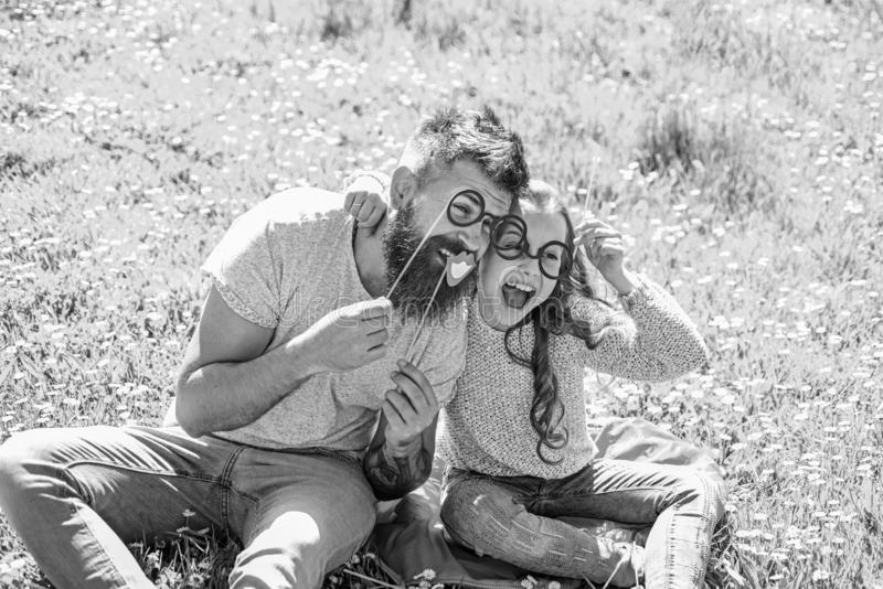 Child and father posing with eyeglases photo booth attributes at meadow. Smart and clever concept. Dad and daughter sits. On grass at grassplot, green royalty free stock image