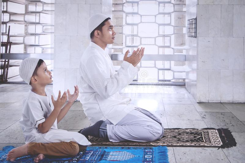 Child with father praying together in the mosque royalty free stock photography