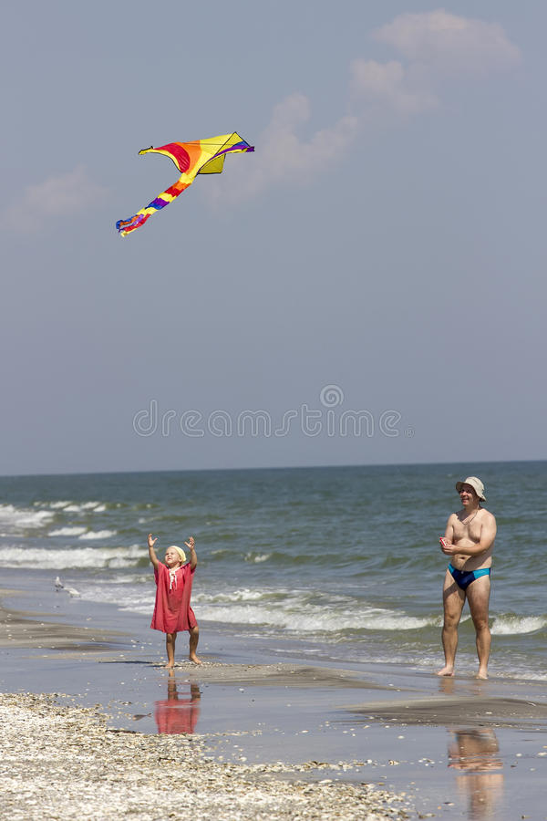 Child and father at the sea side stock photo