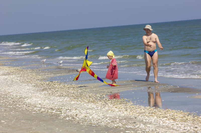 Child and father at the sea side stock photography