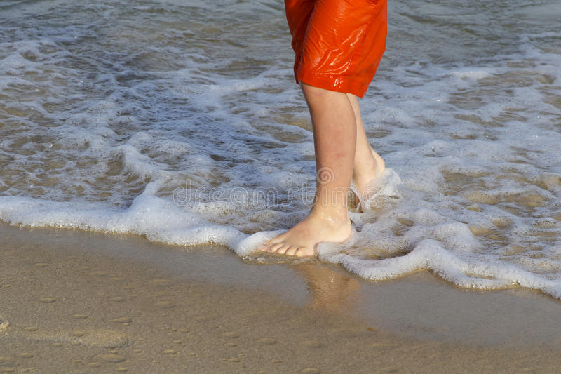 Child feet on beach stock photos