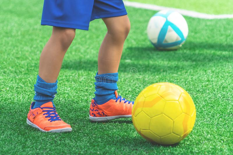 Child feet dribbling Soccer ball on a field. Child feet is dribbling Soccer ball on a field stock photography