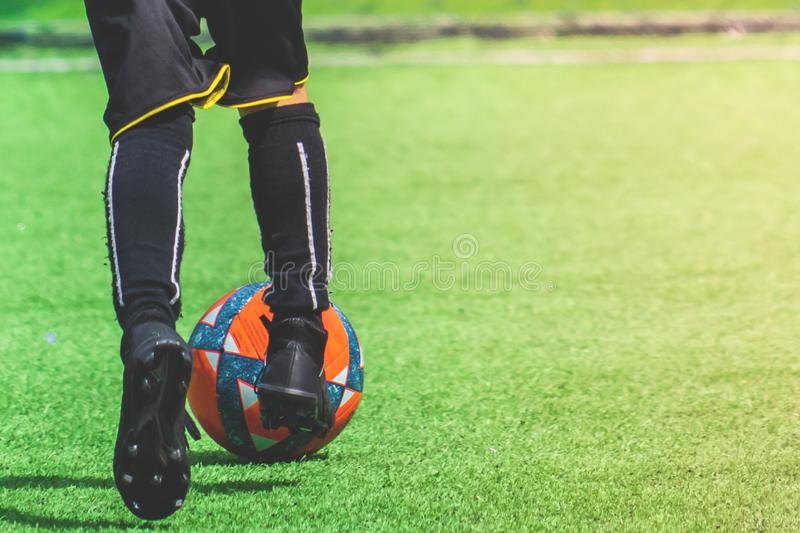 Child feet dribbling Soccer ball on a field. Child feet is dribbling Soccer ball on a field royalty free stock photography