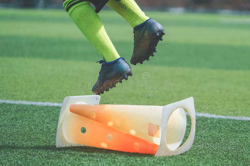 Child feet with football boot practicing Jumping over the cone on soccer field, For children Soccer academy training concept royalty free stock photos