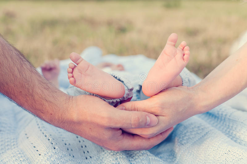 Child feet hold on mother and father hands royalty free stock photos