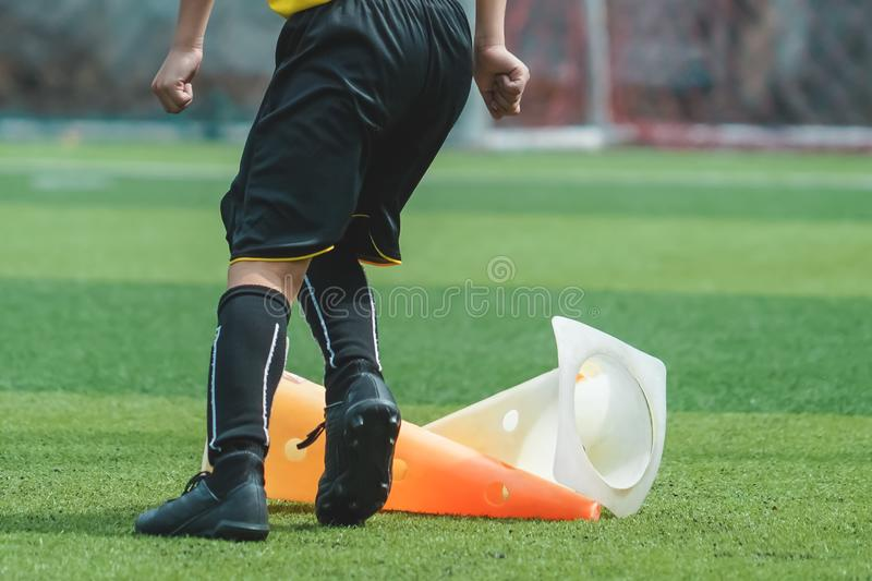 Child feet practicing Jumping over the cone on soccer field royalty free stock photos