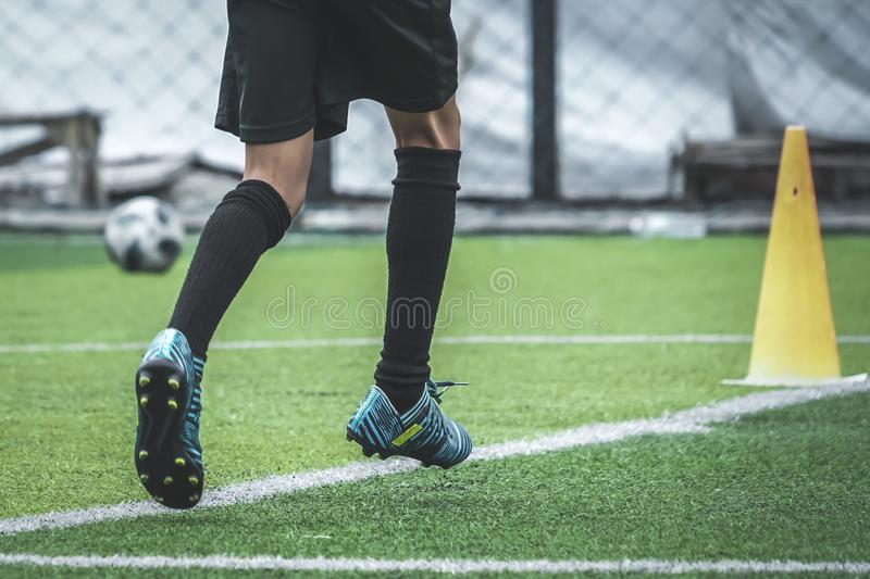 Child feet practicing running and moving on soccer field royalty free stock image