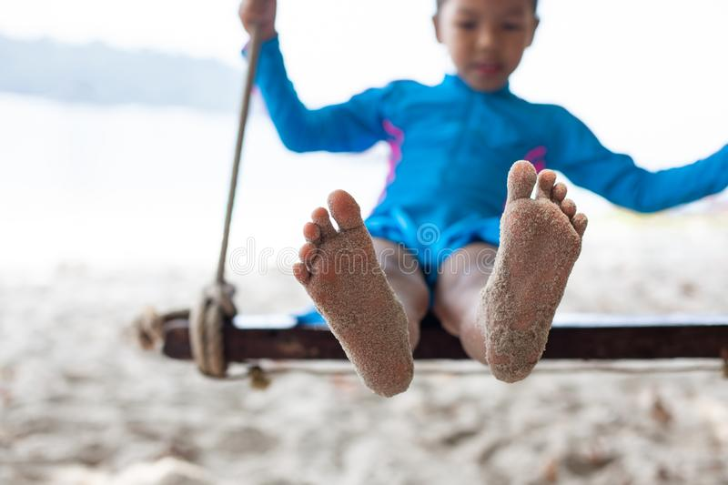 Child feet with sand while she playing on a swing at the beach near the sea royalty free stock photography