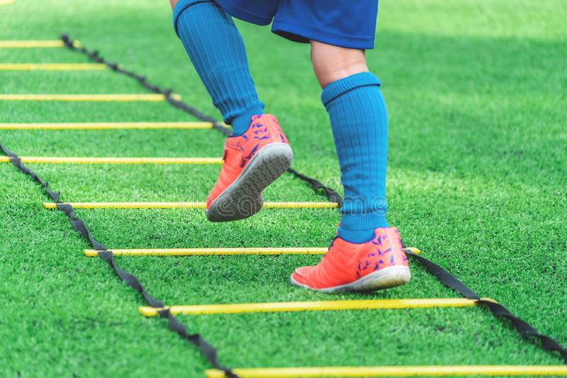 Child soccer boots training on agility speed ladder in soccer training stock photo
